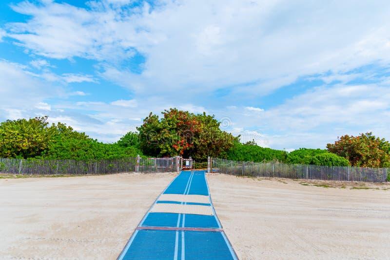 Rampa de acesso da praia para a cadeira de rodas na areia na praia sul fotografia de stock