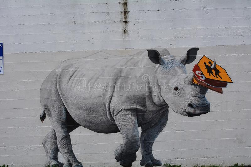 A rampaging rhino in Portland, Oregon. This is the mural of a rhinoceros on a wall in Portland, Oregon with several signs stuck on his horn stock image