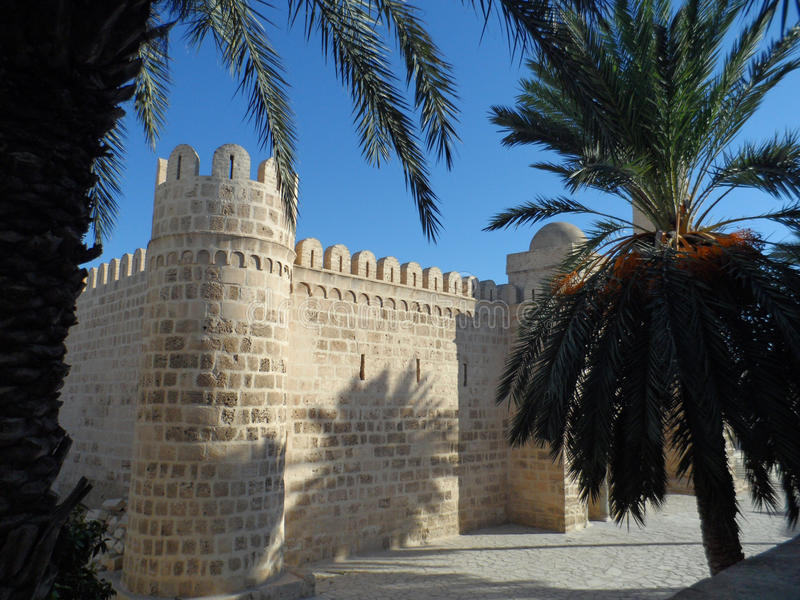 Ramparts Surrounding Old Sousse Medina. Palm trees frame the stone wall ramparts protecting the ancient Sousse Medina in Tunisia, a UNESCO World Heritage Site royalty free stock photo