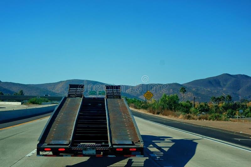 Rampe d'un camion de transporteur de voiture entraînant une réduction l'autoroute photo stock