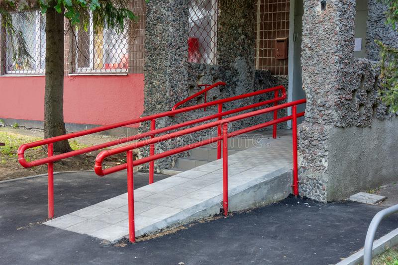 Rampe f?r Rollstuhleintritt mit Metallhandl?ufen Arbeitsunfähige Personen interessieren sich in der städtischen Umwelt stockfoto