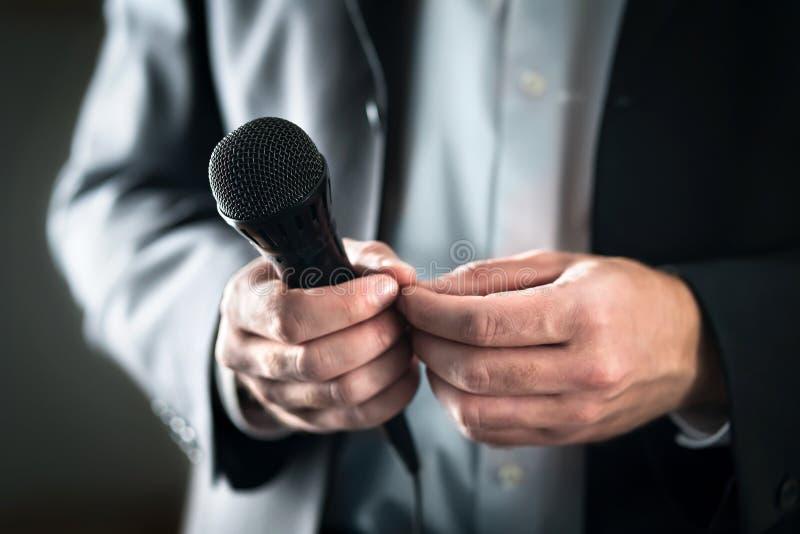 Rampfeberbegrepp Nervös och blyg offentlig högtalare med mikrofonen Affärsman som är rädd av att ge anförande för folkmassa av fo royaltyfri bild