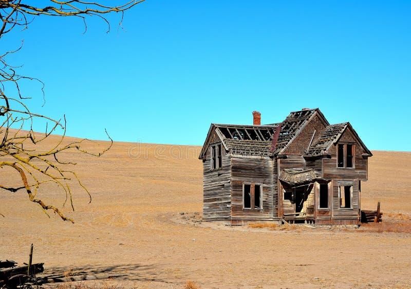 Ramshackle house on barren hillside stock images