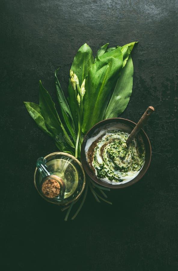 Ramson yoghurtdopp eller dressing i träbunke på mörk lantlig köksbordbakgrund med ingredienser, bästa sikt Sunt arkivbild