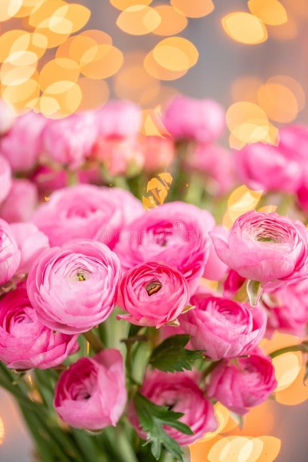 Ranúnculo persa Flores rosadas carmesís del ranúnculo del manojo en el florero de cristal Bokeh de la guirnalda en fondo Papel pi imagen de archivo libre de regalías