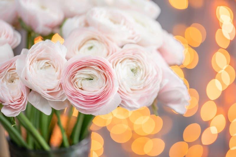 Ranúnculo persa Manojo pálido - flores rosadas del ranúnculo en el florero de cristal Bokeh de la guirnalda en fondo Papel pintad fotografía de archivo libre de regalías
