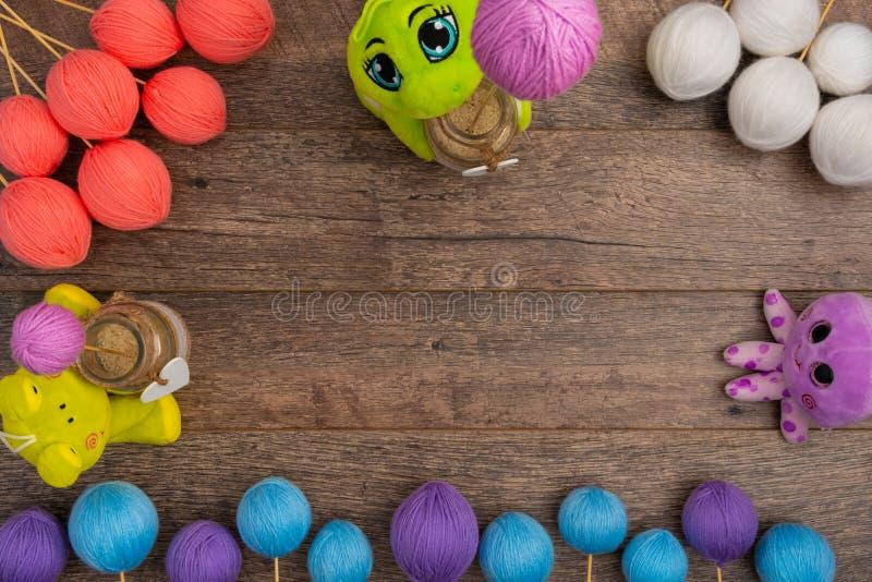 Rana verde de la felpa con las bolas en colores pastel de las lanas foto de archivo