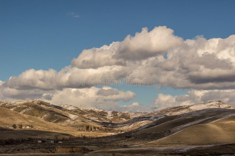 Ranch de collines de pied de l'Idaho après une neige légère sous le ciel bleu et les nuages cassés photo stock