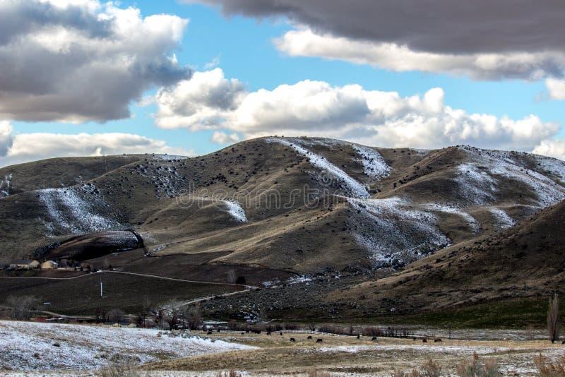 Ranch de l'Idaho au coucher du soleil après une neige légère sous le ciel bleu et les nuages cassés image stock