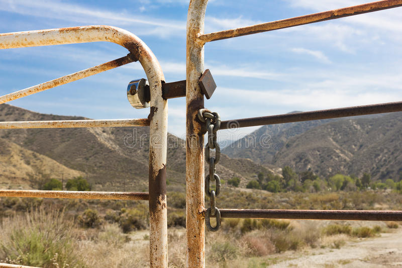 Ranch Gate. Is locked and chained with mountains and brush in the background royalty free stock image