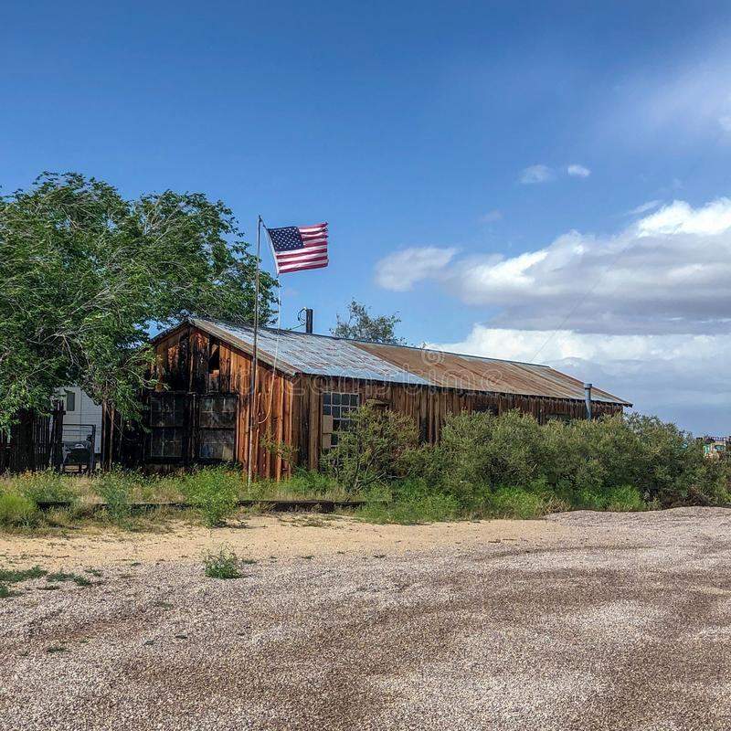 Rancho de madeira velho com a bandeira americana no deserto fotos de stock royalty free