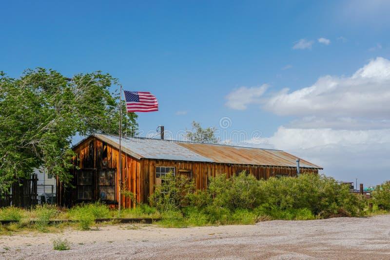 Rancho de madeira velho com a bandeira americana no deserto imagens de stock royalty free