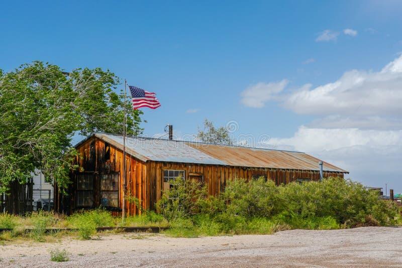 Rancho de madera viejo con la bandera americana en el desierto imágenes de archivo libres de regalías