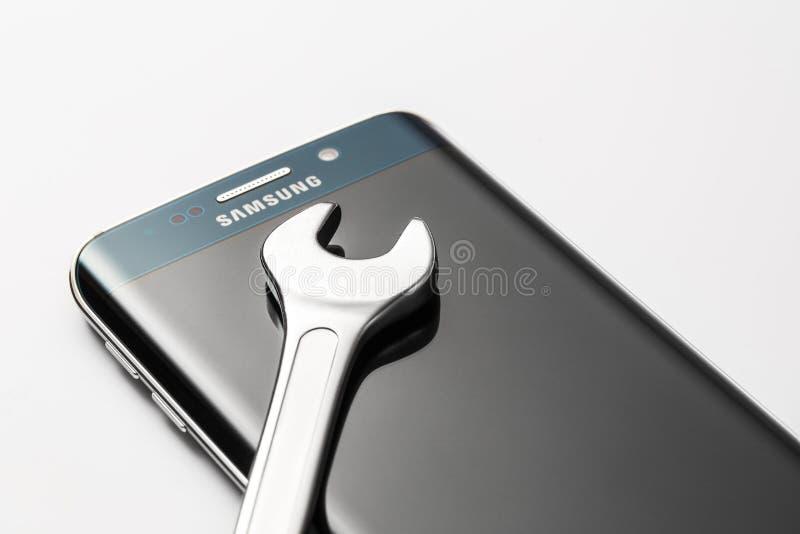 Rand Smartphone des Samsung Galaxy-S6 und Schlüssel, Reparaturkonzept lizenzfreie stockfotos
