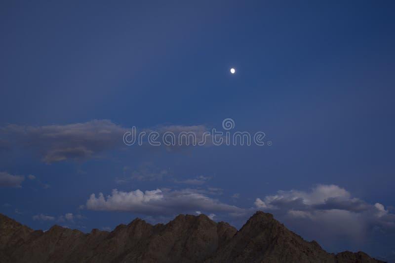 Rand van grijze bruine woestijnbergen onder een donkerblauwe avondhemel met grijze wolken en een volle maan met sterren royalty-vrije stock foto