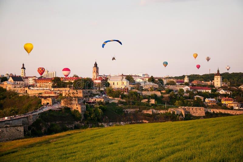 Randig ballong för varm luft som flyger över stad fotografering för bildbyråer