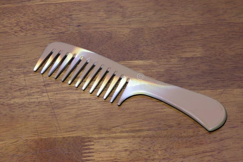 Randig brun färg av hårkammen på trätabellbakgrund royaltyfri fotografi