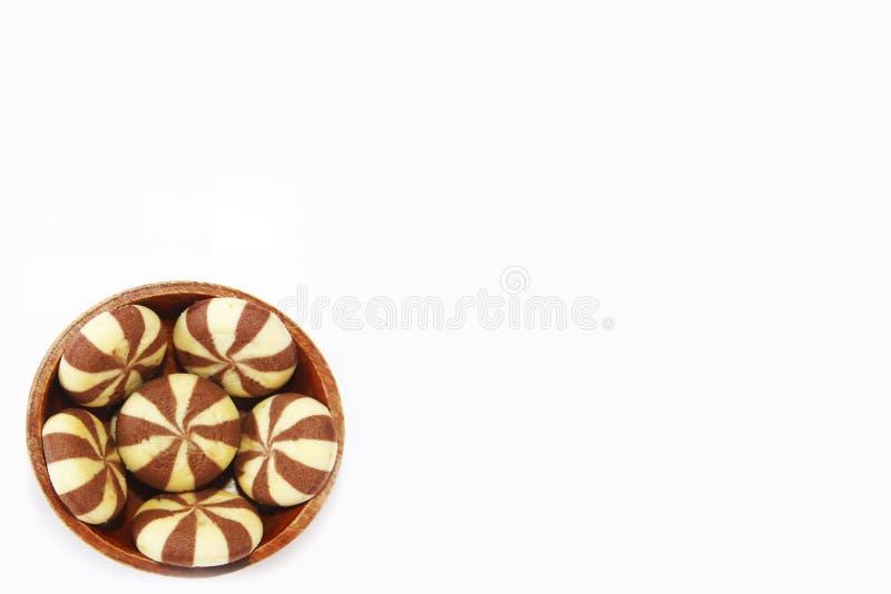 Randiga gula bruna choklade kakor i en brun tr?platta p? en vit bakgrund royaltyfria bilder