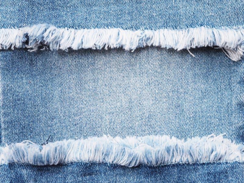Randkader van blauw denim dat over de achtergrond van de jeanstextuur wordt gescheurd royalty-vrije stock fotografie