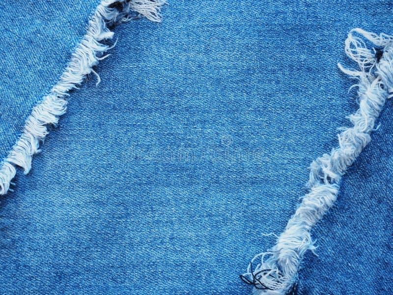 Randkader van blauw denim dat over de achtergrond van de jeanstextuur wordt gescheurd stock afbeeldingen