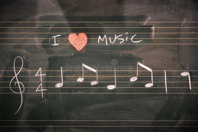 Random music notes written on a blackboard. I love music concept stock images