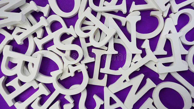 random white wooden alphabet letters on purple background stock images
