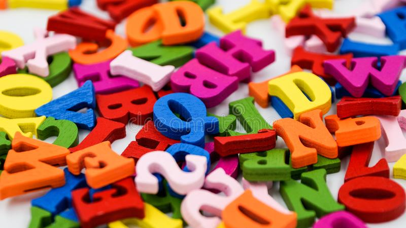 Randomly scattered colorful wooden letters on a white background. Photo royalty free stock photo