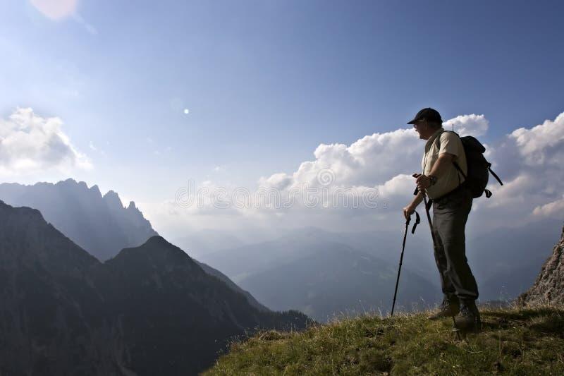 Randonneur aîné appréciant l'horizontal étonnant des Alpes images stock