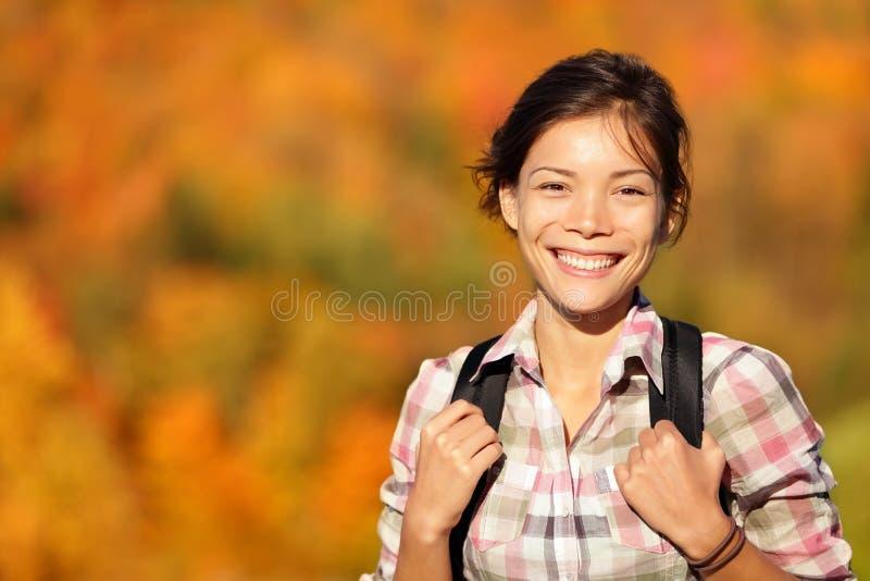 Randonneur asiatique de femme trimardant dans la forêt d'automne photos libres de droits
