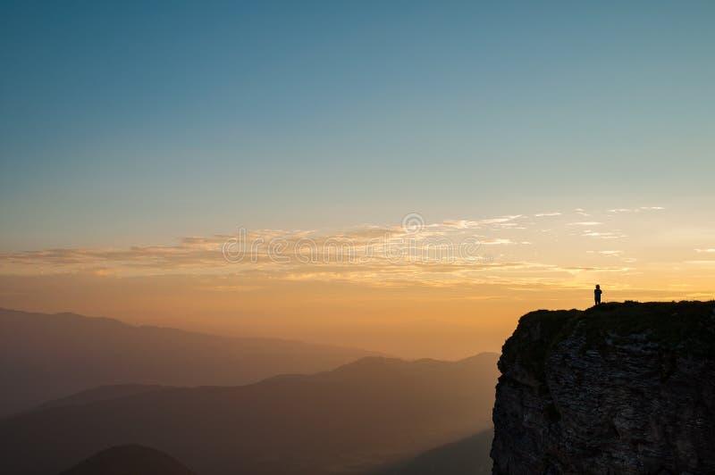 Randonneur au bord d'une montagne à distance au lever de soleil images stock