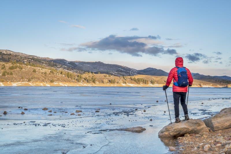 Randonneur au rivage du lac congelé de montagne photo stock
