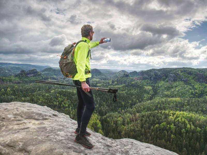 Randonneur avec le téléphone à disposition Spring Valley en montagnes rocheuses image stock