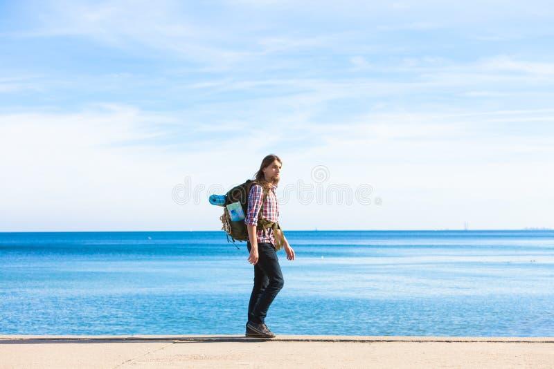 Randonneur d'homme avec le sac ? dos marchant ? pas marqu?s par le bord de la mer image stock