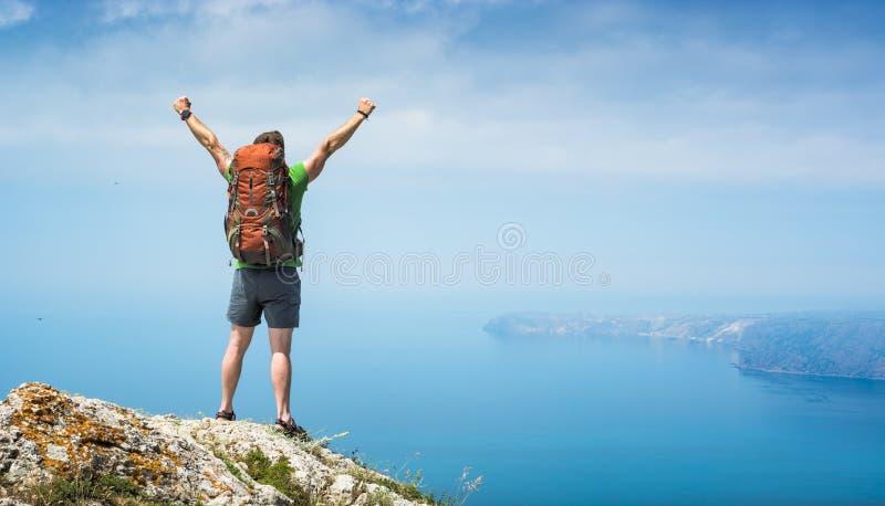 Randonneur d'homme avec les mains augmentées sur un dessus de montagne photo stock
