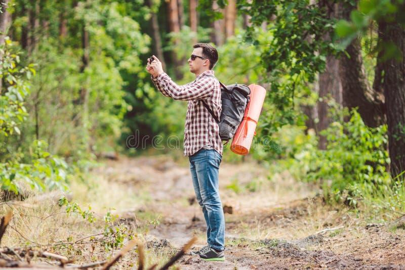 Randonneur d'homme prenant à photo le téléphone intelligent dans le voyageur attirant de forêt faisant la photo avec le téléphone photo libre de droits