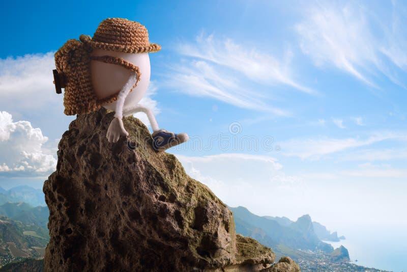 Randonneur d'oeuf de pâques dans un chapeau drôle se reposant sur une falaise images stock
