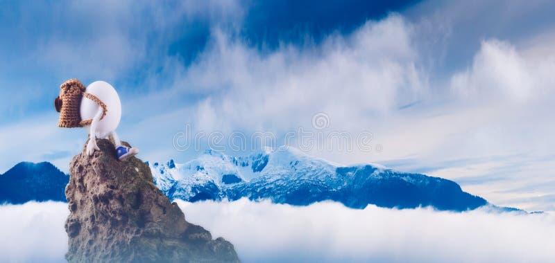 Randonneur d'oeuf de pâques s'asseyant sur une falaise images libres de droits