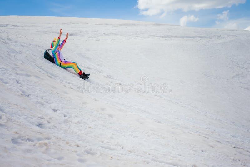 Randonneur dans le costume de licorne glissant en bas de la colline neigeuse images stock