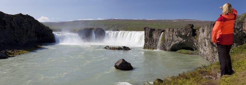 Randonneur de femme à la cascade à écriture ligne par ligne de Godafoss, Islande photos stock