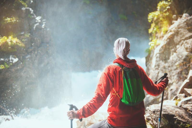 Randonneur de femme avec des bâtons regardant sur la cascade Concept de tourisme images stock