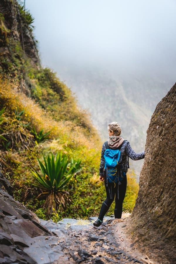 Randonneur de femme avec le sac à dos dans le terrain rocheux sur une traînée étroite à Coculi Santo Antao, Cabo Verde image stock