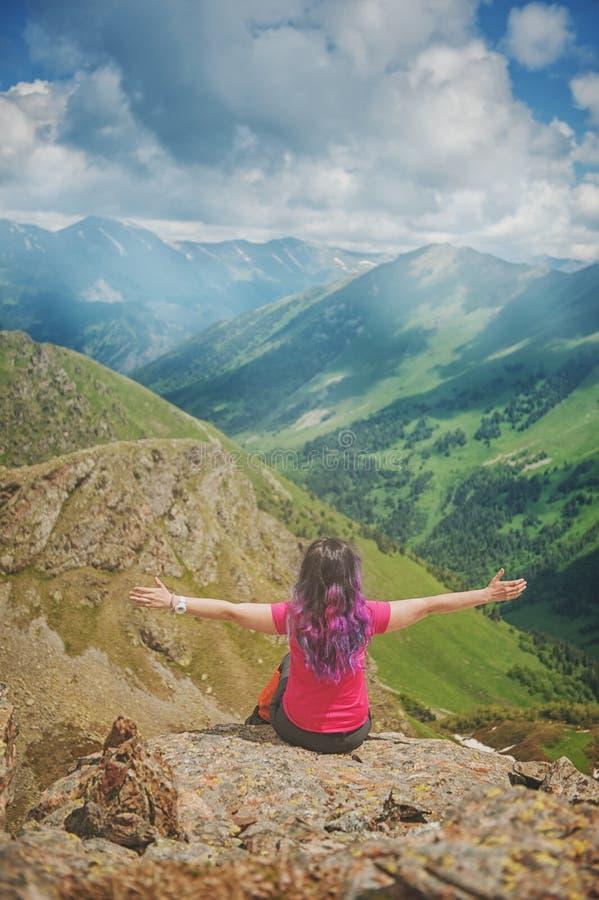 Randonneur de femme avec les cheveux colorés se reposant sur le dessus de la montagne photo libre de droits