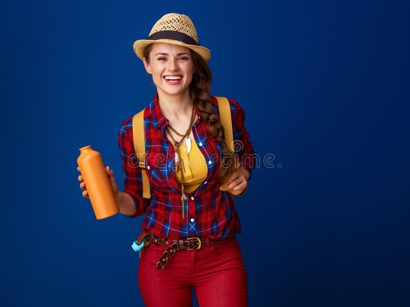 Randonneur de femme d'isolement sur le fond bleu avec la bouteille d'eau photo libre de droits