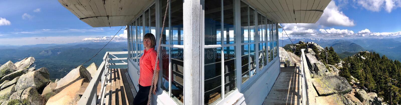 Randonneur de femme par la hutte de surveillance du feu sur le dessus de montagne avec des vues expansives photographie stock libre de droits