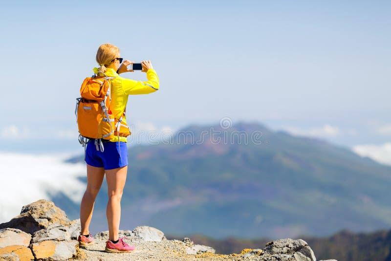 Randonneur de femme prenant des photos en montagnes images libres de droits