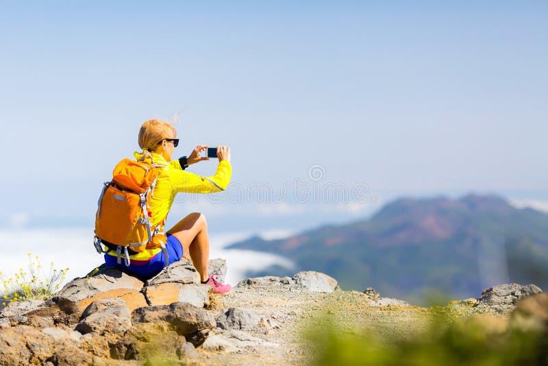 Randonneur de femme prenant des photos en montagnes photos stock