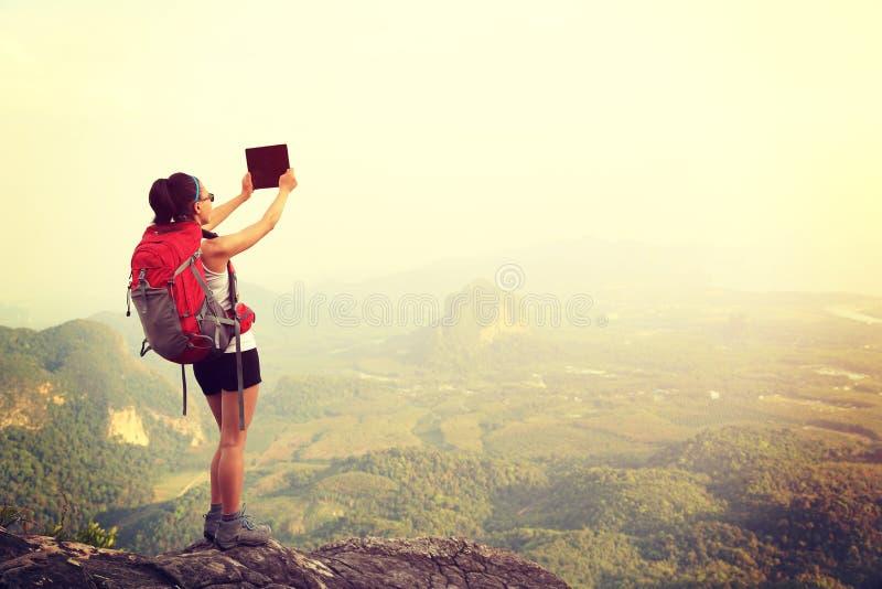 Randonneur de femme prenant la photo avec l'appareil photo numérique photographie stock libre de droits