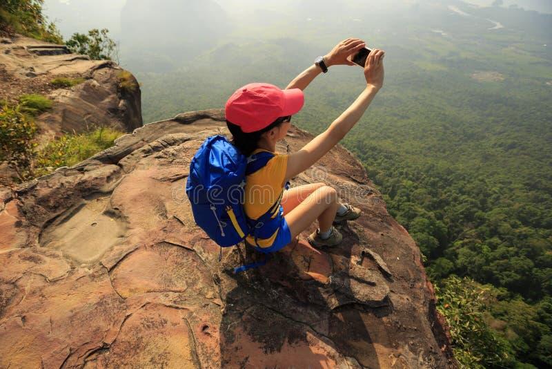 randonneur de femme prenant la photo avec le smartphone sur la falaise de crête de montagne image stock
