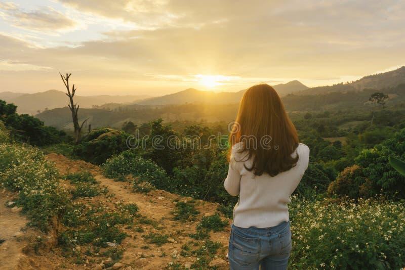 Randonneur de femme prenant la photo avec le téléphone intelligent à la falaise de crête de montagne photographie stock libre de droits