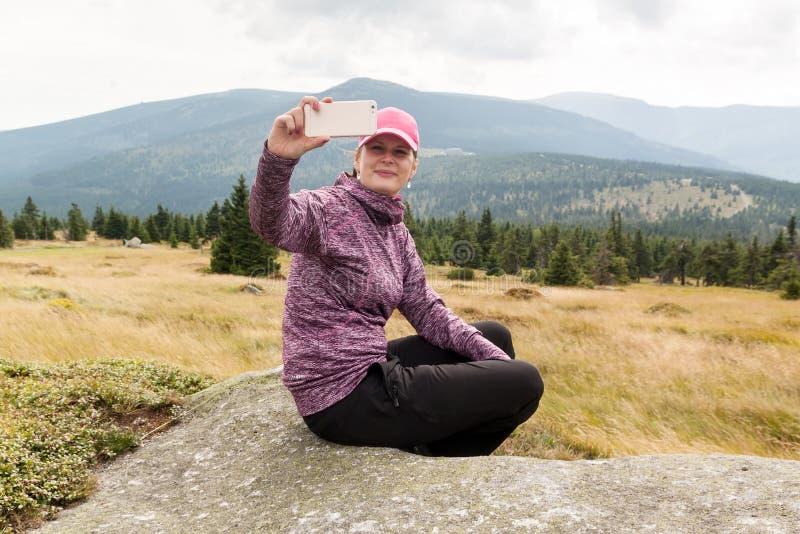 Randonneur de femme prenant le selfie de photo avec le téléphone intelligent à la montagne images libres de droits